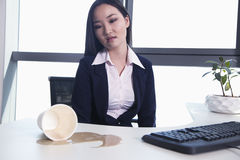 Frustrated Businesswoman spilling coffee Royalty Free Stock Image