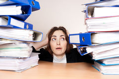 Frustrated businesswoman with stack of folders Royalty Free Stock Image