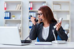 The frustrated call center assistant responding to calls. Frustrated call center assistant responding to calls Stock Photo
