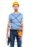 Frustrated carpenter. Frustrated young male carpenter trapped in wire holding drill and keeping mouth open while standing against white background Stock Photography