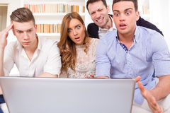 Frustrated casual group of friends sitting on couch looking at l. Shocked and frustrated casual group of friends sitting on couch looking at laptop, pissed off Royalty Free Stock Photography