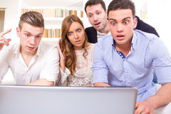 Frustrated casual group of friends sitting on couch looking at l. Shocked and frustrated casual group of friends sitting on couch looking at laptop, pissed off Stock Photo