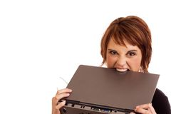 Frustrated Caucasian businesswoman biting laptop. Frustrated Caucasian business woman holding her glasses and biting laptop in anger royalty free stock photos