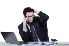 Frustrated caucasian worker talking on cellphone Stock Photo