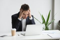 Worried businessman frustrated with bad business news. Frustrated CEO worried reading negative reports about business collapse, falling rates and bankruptcy news royalty free stock images