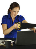 Frustrated Computer User. A woman frustrated with her laptop tries to cut it with a saw Stock Photo