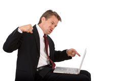 Frustrated computer user punches laptop. Frustrated caucasian business man sitting in suit and red tie pointing at a laptop ready to punch it on isolated white Stock Photography
