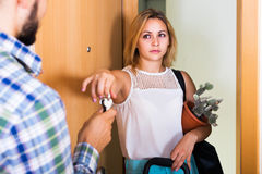 Frustrated couple standing at doorway Stock Images