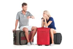 Frustrated couple waiting departure with luggage. Royalty Free Stock Images