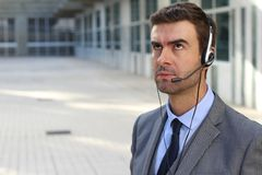 Frustrated customer service worker rolling his eyes.  Royalty Free Stock Image