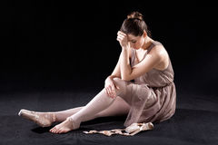 Frustrated dancer. Frustrated, discouraged ballet dancer with tired feet royalty free stock images