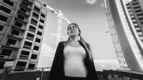 Frustrated and depressed woman posing against skyscrapers under Royalty Free Stock Photo