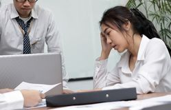 Frustrated depressed young Asian business woman with hands on face suffering from severe problem between meeting in office. Frustrated depressed young Asian Royalty Free Stock Image