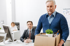 Frustrated elderly employee leaving office with box full of belongings. Quitting my responsibilities here. Fired involved aging employee standing and holding the Royalty Free Stock Images