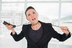 Frustrated elegant businesswoman with telephone cable around her neck. Frustrated young elegant businesswoman with telephone cable around her neck at a bright Stock Images