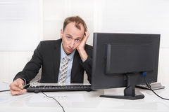 Frustrated employee sitting and desk holding his head - problems. Frustrated employee sitting and desk holding his head - headache or migraine stock photo