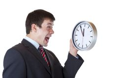 Frustrated employee with time pressure cries. Frustrated employee holds clock in front and shouts enervated.Isolated on white background Stock Image