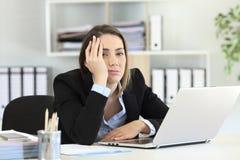 Frustrated executive looking at camera at office. Frustrated executive posing looking at camera on a desktop at office stock photo