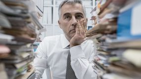 Frustrated executive overloaded with paperwork. Frustrated overwhelmed executive working in the office and overloaded with paperwork, he is leaning on his arm Stock Images