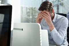 Frustrated executive sitting near the window with hand on head royalty free stock images