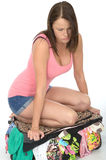 Frustrated Fed Up Young Woman Trying to Close an Overflowing Suitcase by Kneeling on It. With clothes spilling out, looking away from camera, wearing a pink Royalty Free Stock Photography