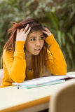 Frustrated female college student doing homework Stock Photos