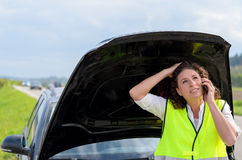 Frustrated female driver calling for help Royalty Free Stock Image