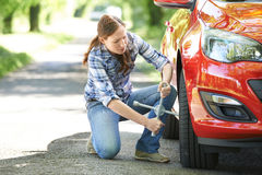 Frustrated Female Driver With Tyre Iron Trying To Change Wheel Stock Photography