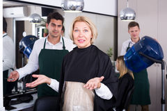 Frustrated female pensioner having fight with hairdresser Stock Images
