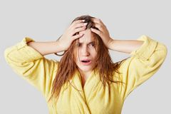 Frustrated female touches head, has wet hair and disorder, doesn`t know what to wear and which hairstyle make for meeting, dressed. In casual domestic clothing Royalty Free Stock Photo