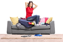 Frustrated girl packing a lot of clothes into one bag Stock Image