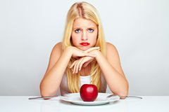 Frustrated girl with red apple Royalty Free Stock Photos