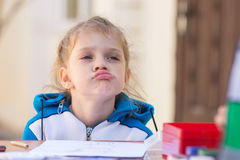 Frustrated girl sitting at a table in courtyard of the house and looking cocky Stock Images