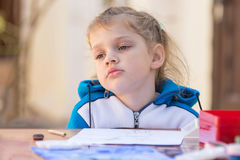 Frustrated girl sitting at a table in yard and sad looks nowhere Royalty Free Stock Photography