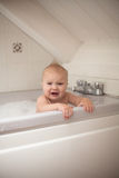Frustrated grimace kid looks out of  bathroom, bathing in  bathr Royalty Free Stock Photos