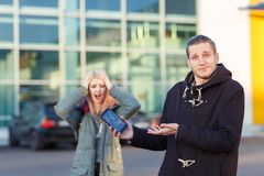 A frustrated guy is holding a smartphone with a broken screen, in the background a girl screams and clings to her head. Stock Photos