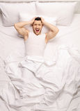 Frustrated guy lying in bed Royalty Free Stock Images