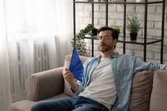 Free Frustrated Guy Recline On Sofa Cool Down With Hand Fan Stock Photos - 212613173