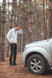 A frustrated guy, standing near a broken car and holds his head. royalty free stock image