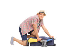 Frustrated guy trying to pack clothes into suitcase Royalty Free Stock Images