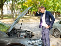 A frustrated guy stands near a broken car, looks under the hood and clings to his head. Outside. Royalty Free Stock Image