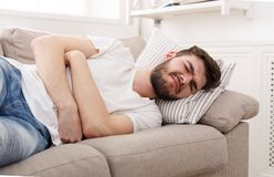 Frustrated handsome young man with stomachache. Terrible stomachache. Frustrated handsome young man hugging his belly and keeping eyes closed while lying on he Royalty Free Stock Image