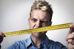 Frustrated handy man. Man holding tape measure Stock Photography
