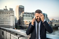 Frustrated hipster businessman with smartphone in the city, making a phone call. Angry and frustrated hipster businessman with smartphone standing on the bridge stock photography