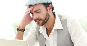 Frustrated hipster businessman using his laptop. In office stock footage