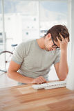 Frustrated hipster sitting at computer desk Royalty Free Stock Photography