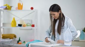 Frustrated housewife looks at blouse hole burned with iron housekeeping problem. Stock footage stock video