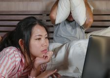 Frustrated husband moody in bed ignored by his workaholic Asian wife or internet social media addict girlfriend using laptop in royalty free stock images