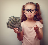 Frustrated kid girl in glasses holding dollars in hand  Stock Photos