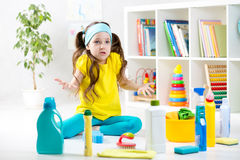 Frustrated kid sitting on floor with cleaning Royalty Free Stock Photos